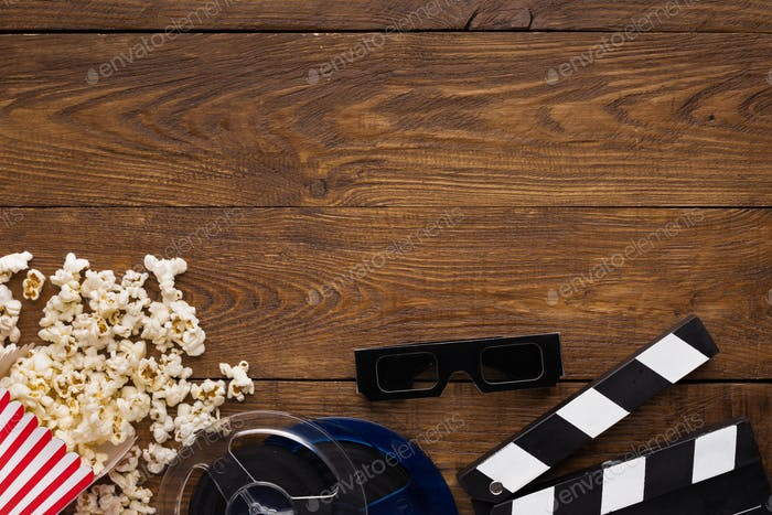 Clapperboard, film reel and popcorn on wooden background, top view