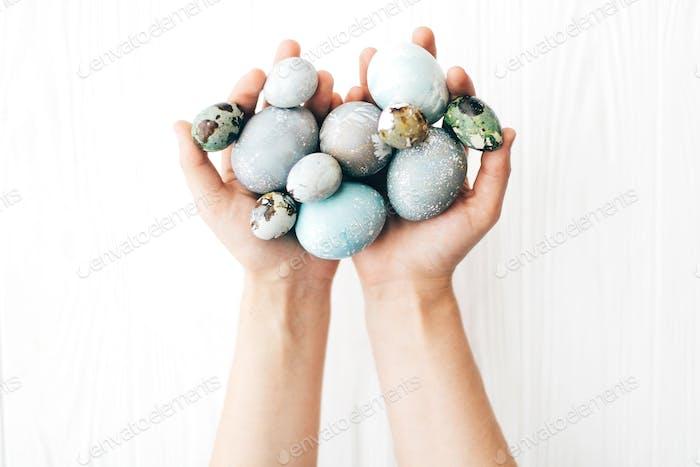 Hände halten stilvolle Ostereier auf weißem Holzhintergrund