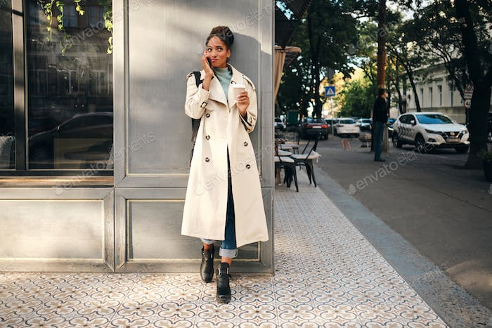 African American girl in stylish trench coat thinking while talking on cellphone on city street