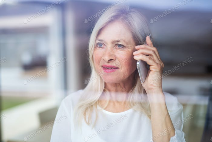 Portrait of senior woman standing indoors at home, using smartphone