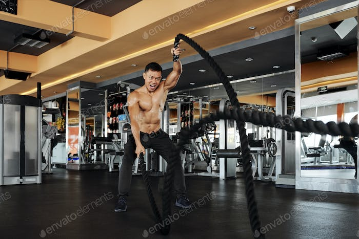 Man exercising with battle rope