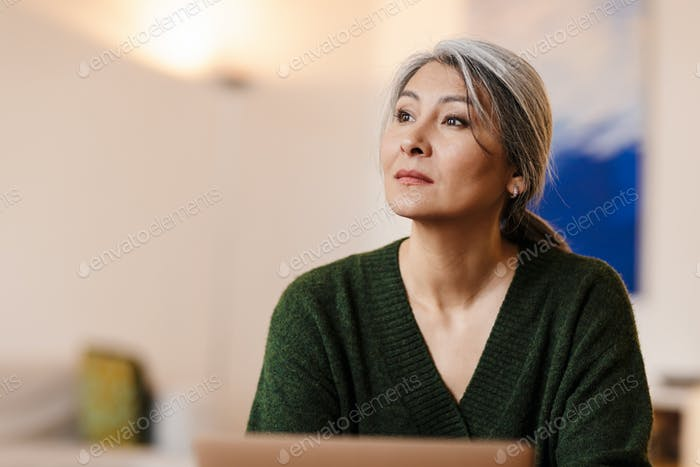 Beautiful grey-haired woman using laptop computer indoors.