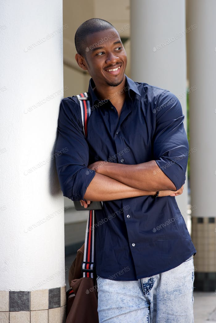smiling young black man with bag leaning against wall