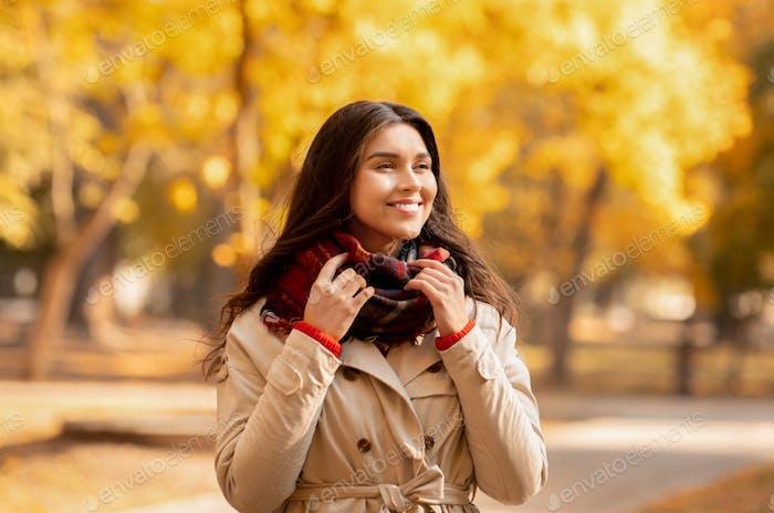 Schöne Millennial-Dame im Mantel und warmen Schal genießen bunte Jahreszeiten im Herbstpark