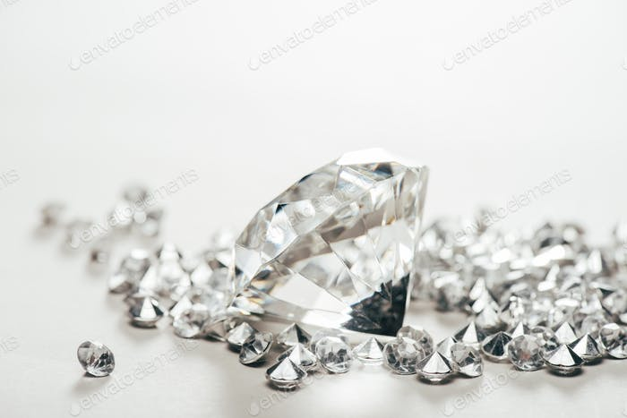 selective focus of sparkling pure big diamond among small on white background