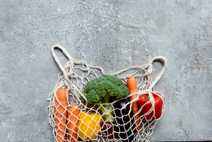 top view of fresh ripe vegetables in string bag on grey concrete surface