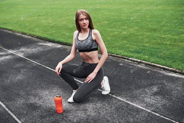 Nadie dijo que sería fácil. Foto de la chica de fitness descansar después de correr por la mañana en el estadio