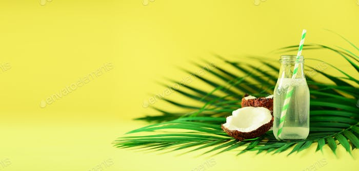 Bottle of coconut water and fresh ripe fruits on yellow background. Summer food concept. Vegetarian