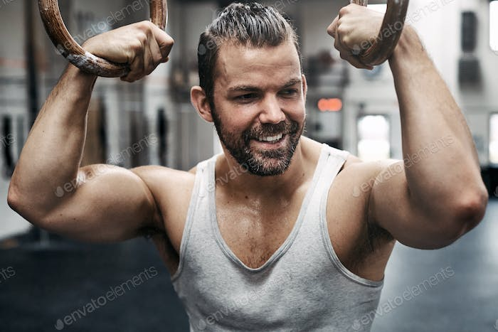 Fit man smiling and exercising on rings in a gym
