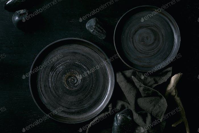 Empty black ceramic plates with black stones