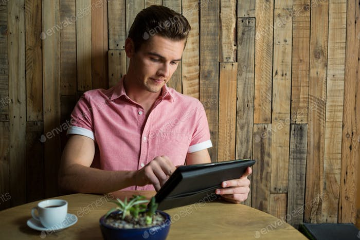 Man using tablet computer at table in coffee house