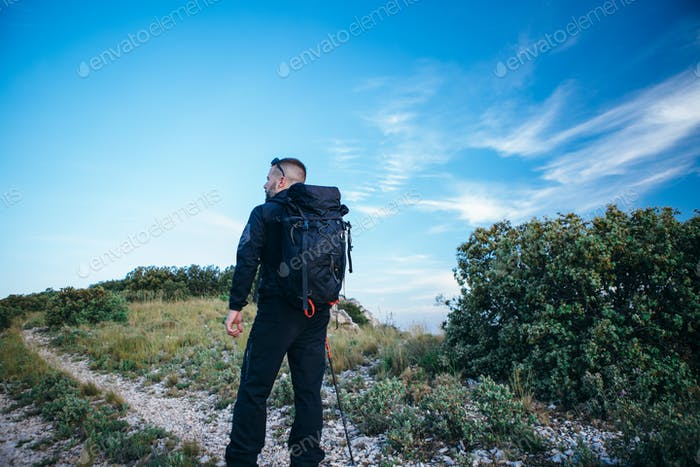 Traveler with backpack on mountain path