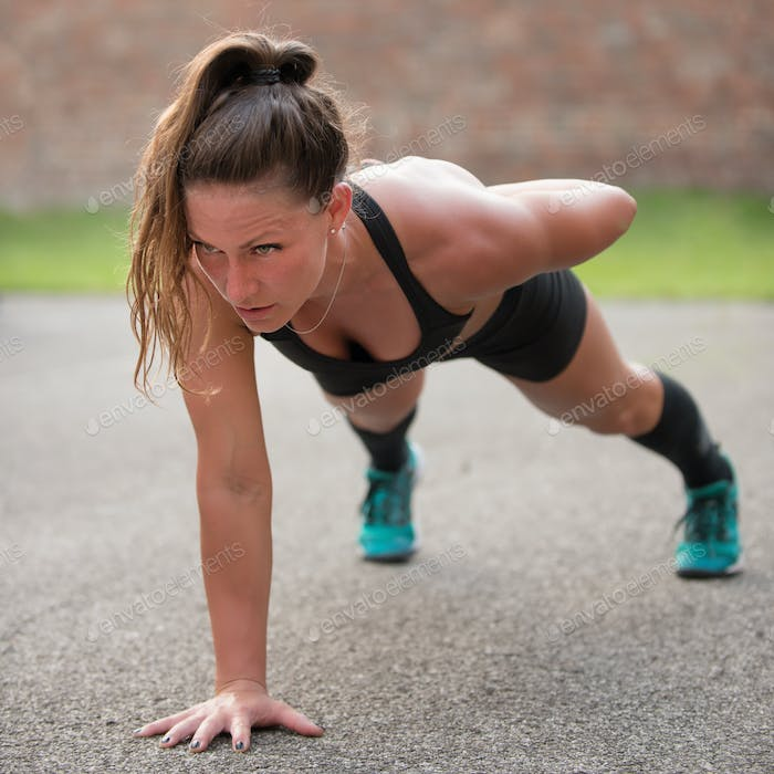 Female athlete doing one arm push-ups