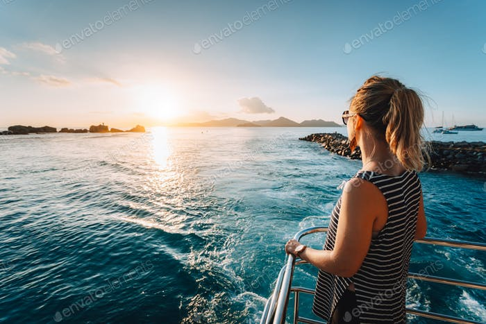 Arriving at La Digue Island, Seychelles. Young adult women enjoying sunset in ocean from Ferry boat