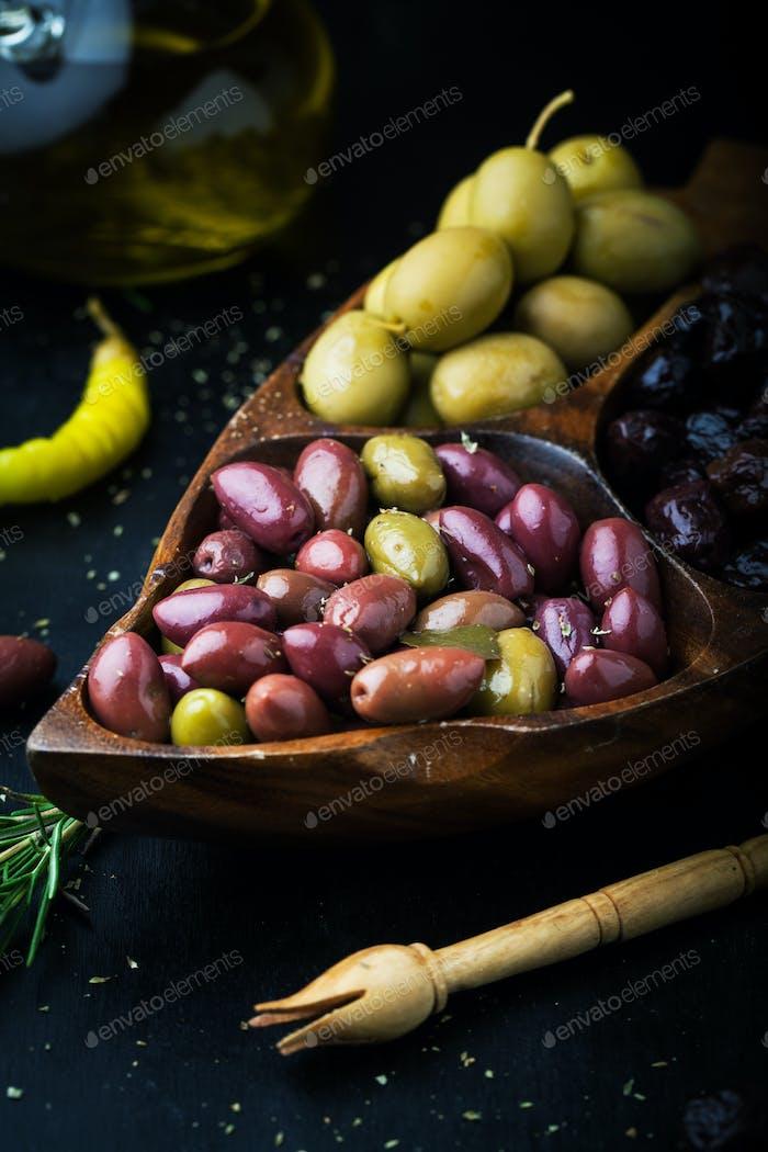 Verschiedene marinierte Oliven mit Kräutern und Rosmarin
