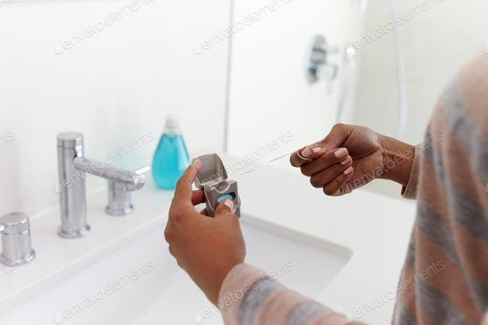 Nahaufnahme der Frau mit Zahnseide aus Pack In Bad