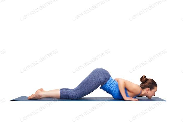 Sporty fit yogini woman practices yoga asana Ashtangasana