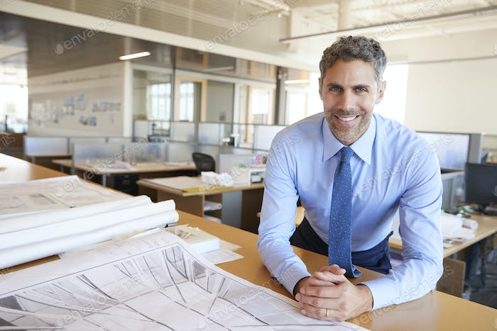 Male architect leaning on desk with plans looking to camera