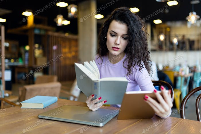 Young woman reading book and holding tablet