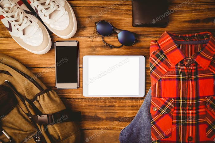 Shirt shoes glasses next to wallet smartphone and bag on wooden table