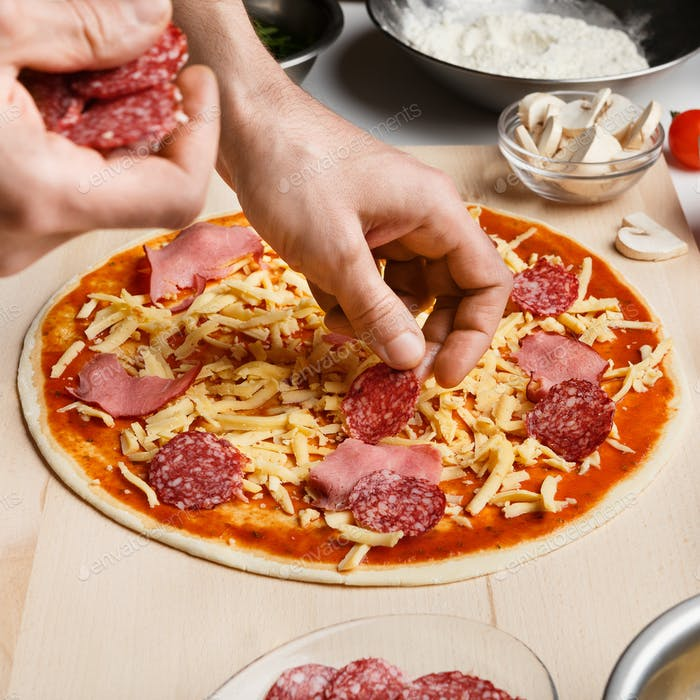 Chef putting salami over cheese on raw pizza