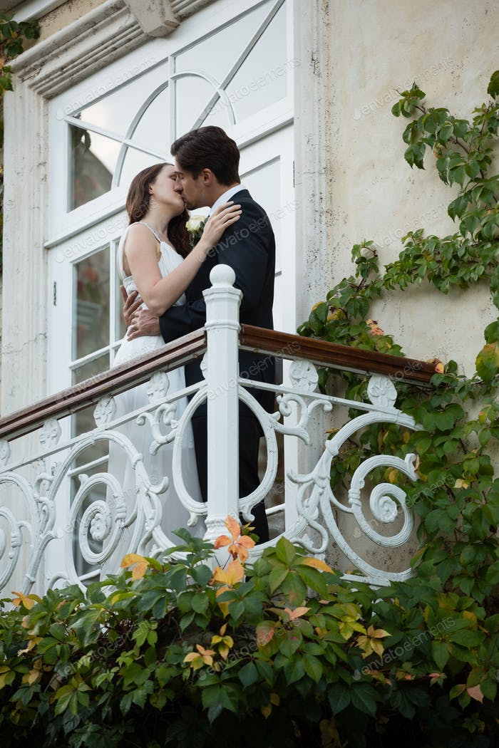 Low angle view of couple kissing while standing in balcony