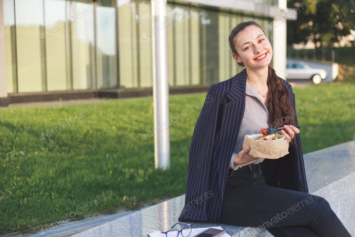 Young business woman eating salad on lunch break in city