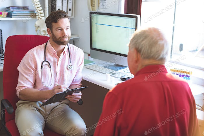 Caucasian male doctor talking to Caucasian senior patient while holding medical report in clinic