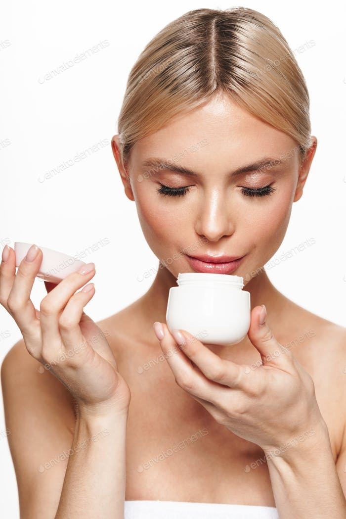 Image of beautiful pleased shirtless woman smelling face cream