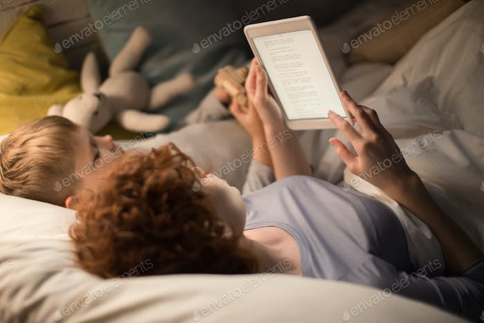 Mother and Son Reading Fairytales in Bed