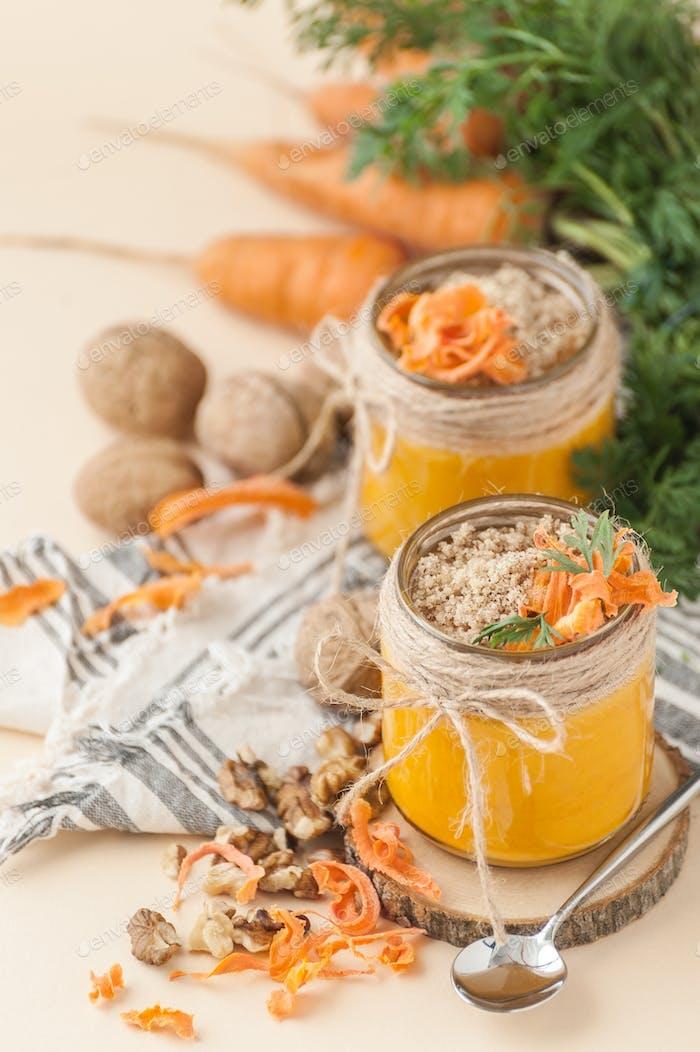 Zwei Gläser Karottenpudding mit einer Walnuss auf einem leichten Pfirsichrücken