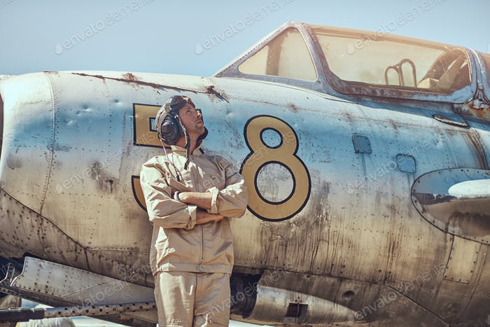Mechanic in uniform and flying helmet standing near an old war fighter-interceptor