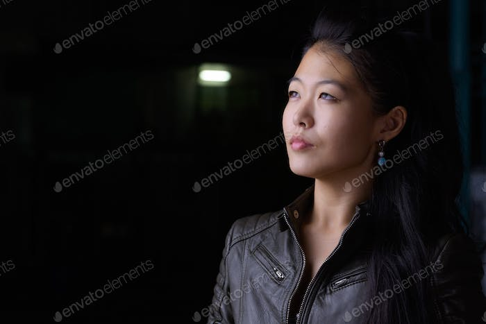 Face of beautiful Asian rebellious woman thinking and looking up outdoors at night