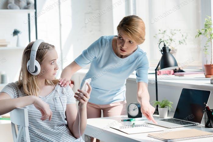 madre obligando a su hija a hacer los deberes mientras escucha música con auriculares
