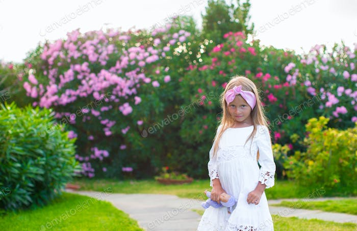 Adorable little girl in exotic resort at sunset during summer vacation