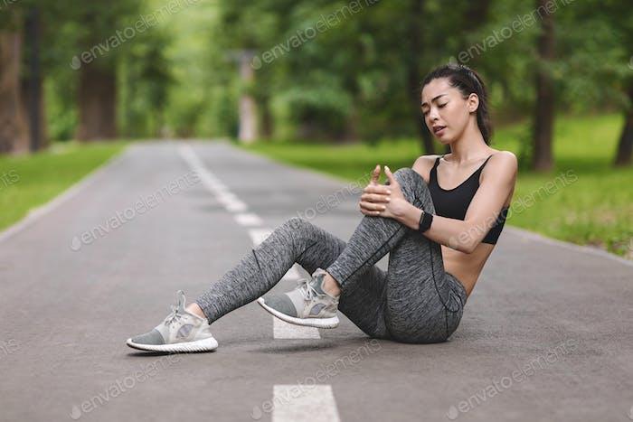 Knieschmerzen. Junge sportliche Frau massiert schmerzhaft verletzten Bein, leidet unter Trauma