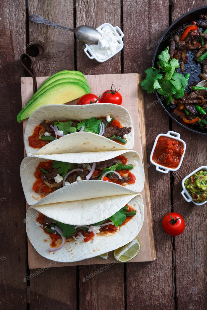 Above view of wheat wraps with mexican pork fajitas, selective focus