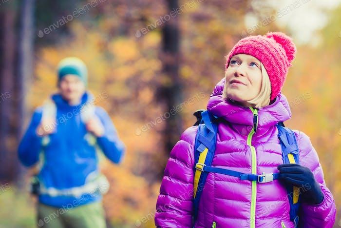 Hombre y Mujer Alegre pareja caminantes caminando en los bosques de otoño