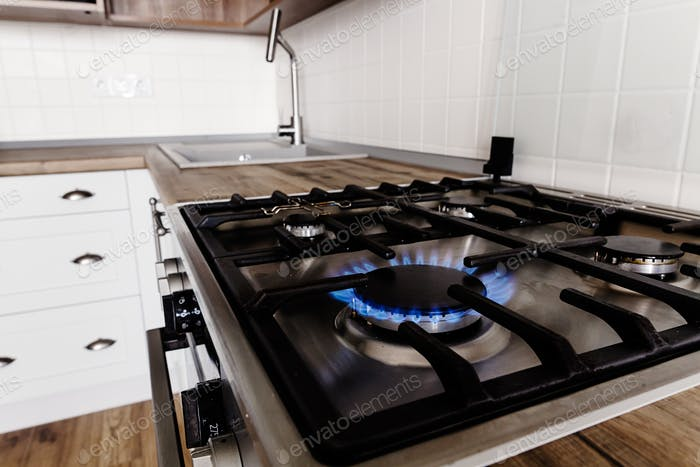 Burning gas from kitchen stove on background of stylish kitchen interior