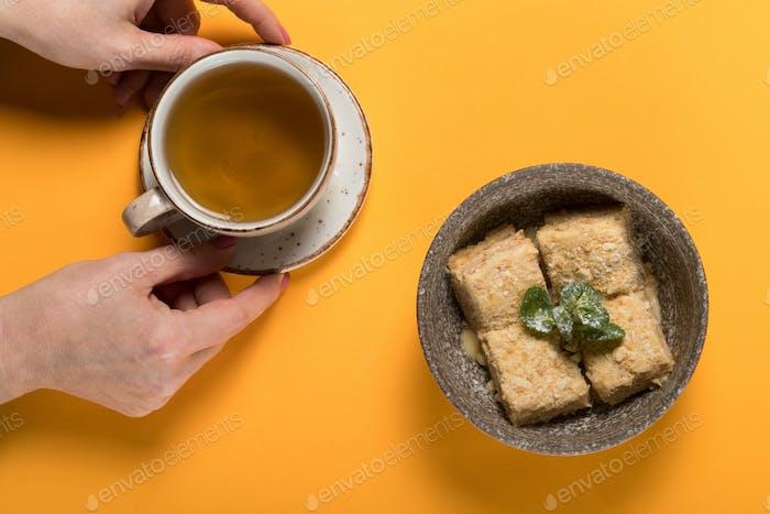 Süßes Dessert mit Tee auf einem farbigen Hintergrund