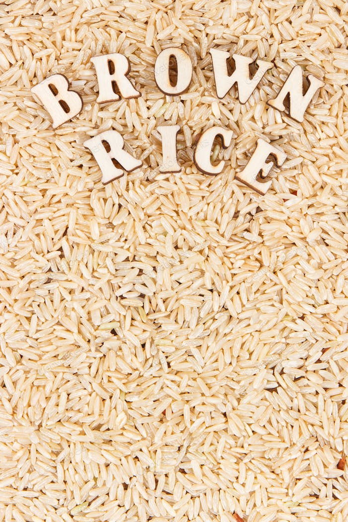 Heap of brown rice as background, healthy gluten free food concept, copy space for text