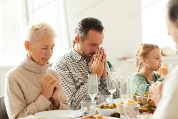 Family praying at the dining table