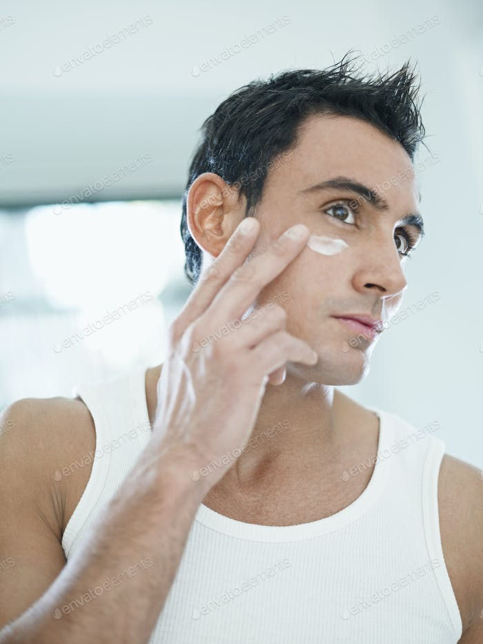Junge gutaussehende Mann Anwendung Hautcreme auf Gesicht