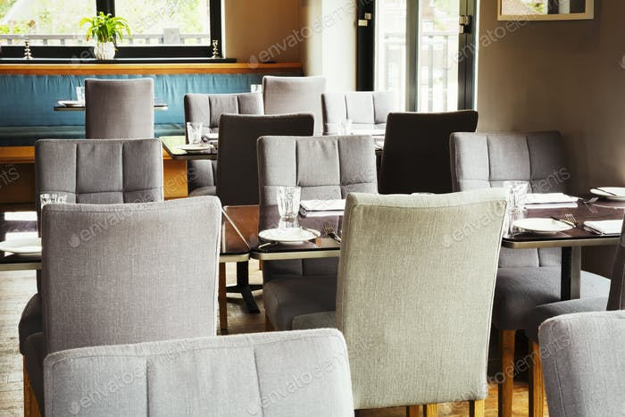 View of tables and grey upholstered chairs in a restaurant.