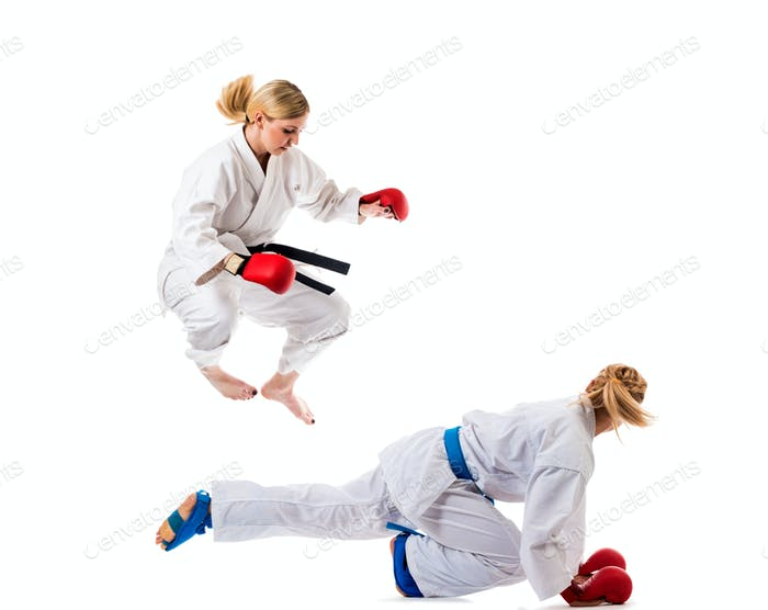 Cute blonde girls training karate on white