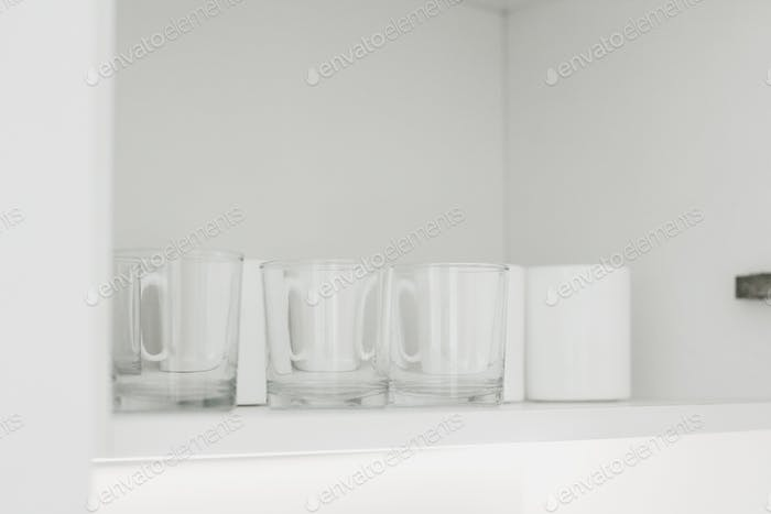 Transparent glasses and white ceramic cups on white shelf in modern white kitchen