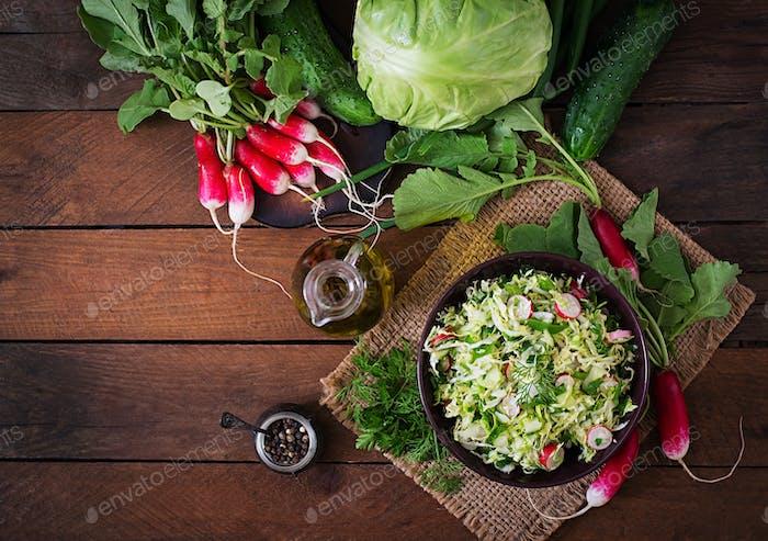 Vitaminsalat aus jungem Gemüse: Kohl, Rettich, Gurken und frische Kräuter. Ansicht von oben