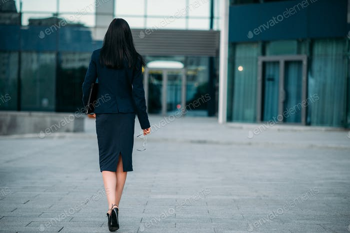 Business woman with laptop in hands, back view