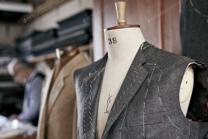 Handmade suit with stiching visible hanging on mannequin