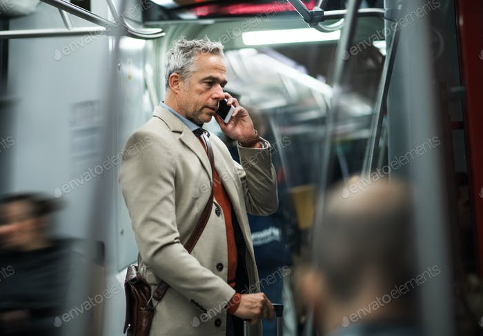 Mature businessman with smartphone travelling by subway in city.